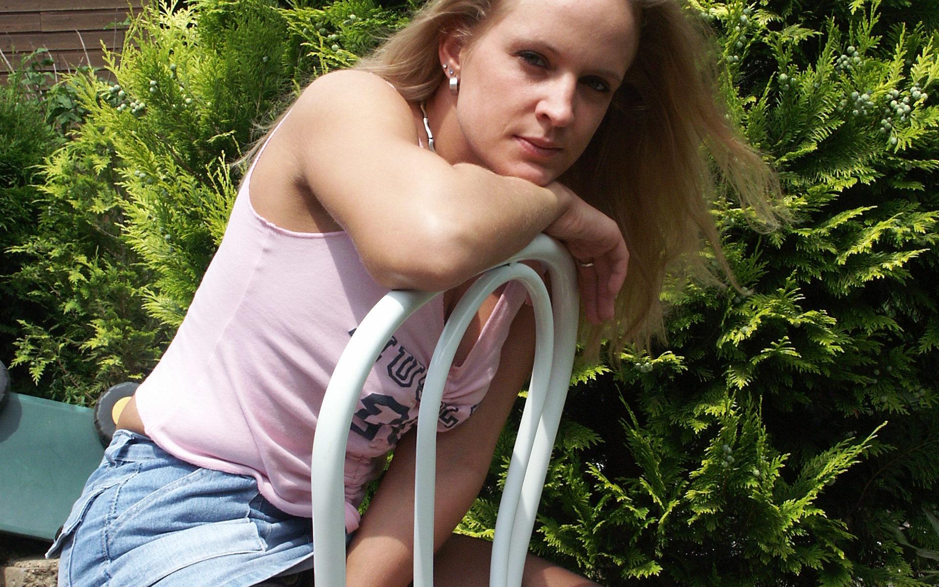 Blonde im Unterhemd sitzt auf Stuhl im Garten